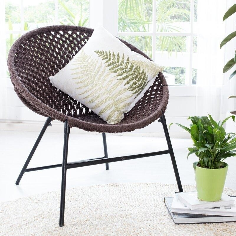 a cozy nook with a brown woven papasan chair, a botanical pillow, a potted plant on a stack of books