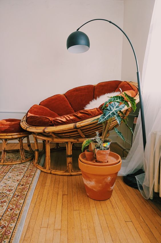 a cozy reading nook with a rattan papasan chair and a footrest with rust velvet covers, a floor lamp and potted plants