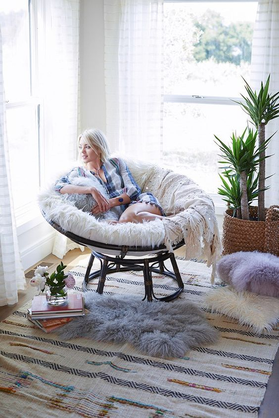 a cozy reading nook with a sark papasan chair, potted plants, pillows and rugs and a stack of books