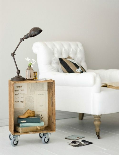 a cozy reading nook with a white chair on casters and a crate side table on casters, too, with a lamp and some vases