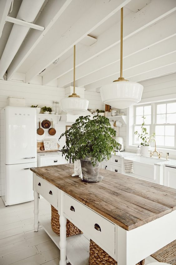 a cozy white farmhouse kitchen with vintage cabinetry, a kitchen island with a wooden top, potted herbs and pendant lamps