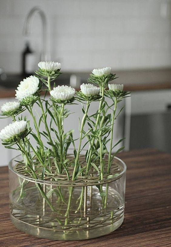 a creative spring centerpiece of a glass bowl with numerous white blooms is a stylish decoration to make