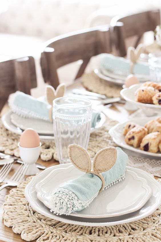 a cute Easter tablescape with woven placemats, blue napkins with bunny ears, eggs and chic glasses