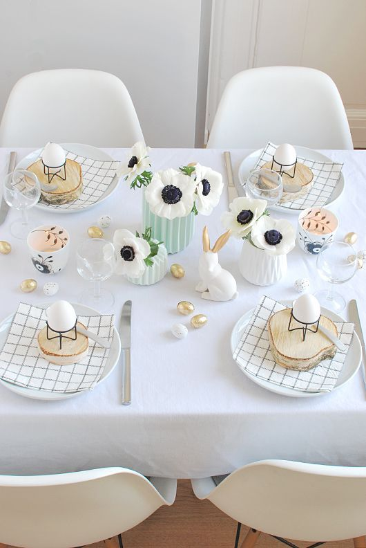 a cute and simple Easter tablescape with printed napkins, wood slices with eggs on stands, white blooms, bunnies and faux mini eggs