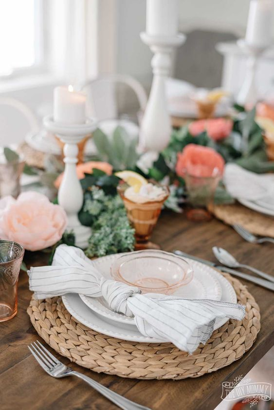 a cute spring table setting with woven chargers, striped napkins, pink glasses and pink and coral blooms plus candles