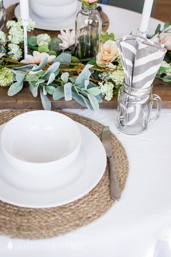 a cute spring table setting with woven placemats, a wooden table runner with blooms and greenery, printed napkins and white porcelain
