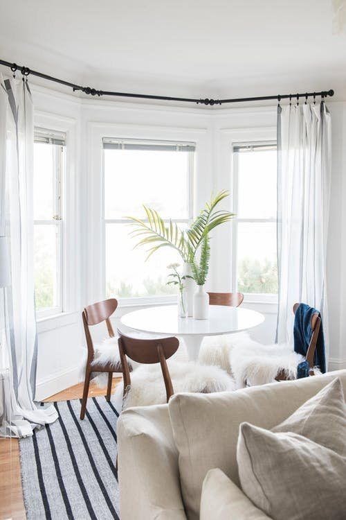 a dining space by the bay window, with a round table, modern chairs and greenery in vases to enjoy the view while eating