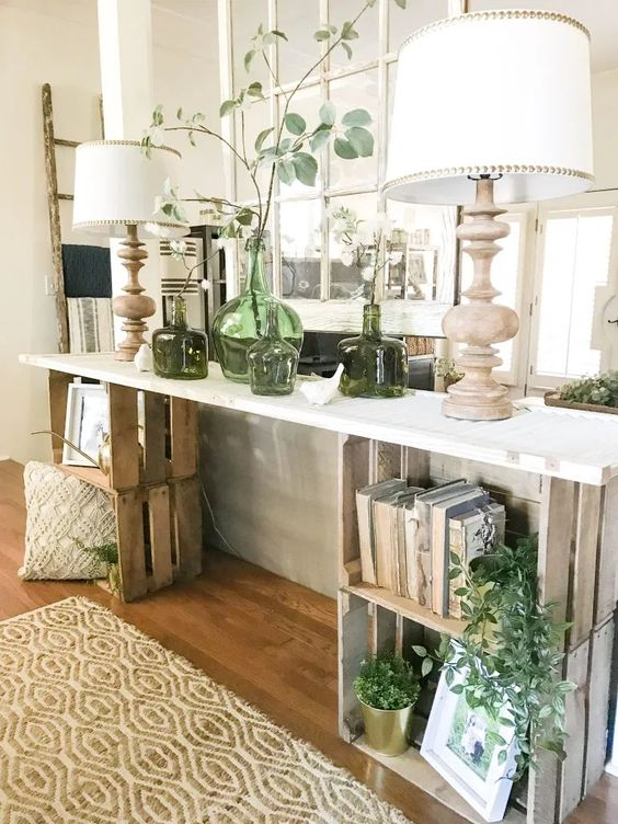 a farmhouse console table with crates and a tabletop placed on them, with books, pillows and greenery and vases is lovely