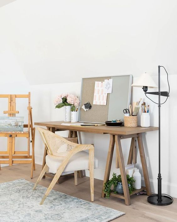 a farmhouse home office with a wooden trestle desk, a rattan chair, potted blooms and greenery and a memo board with stickers