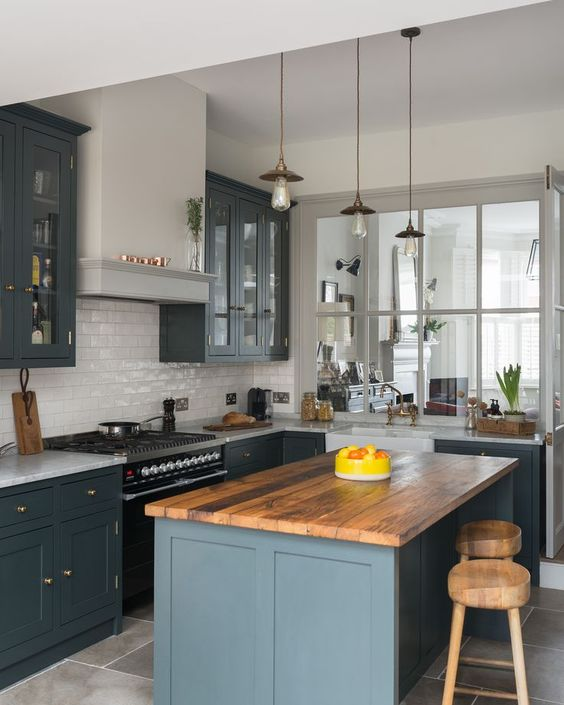 a farmhouse kitchen with grey cabinets, a white subway tile backsplash, a butcherblock countertop, pendant lamps and a wooden stool