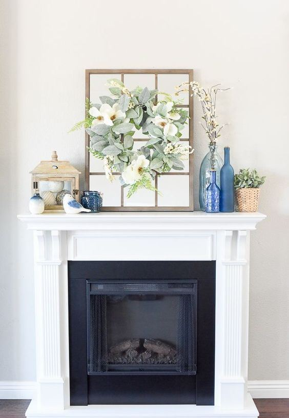a farmhouse spring mantel with blue bottles, decorative balls in a glass box, potted greenery and a faux greenery and a bloom wreath