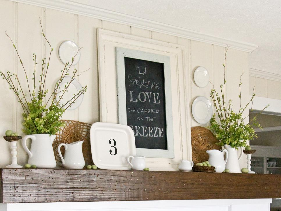 a farmhouse spring mantel with green branches in jugs, faux green eggs, an artwork and plates