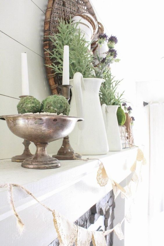 a farmhouse spring mantel with moss balls in a bowl, candles, jugs, greenery and thistles, a wreath and blooms