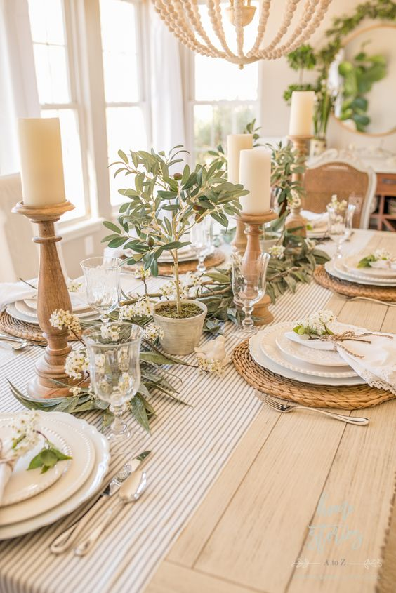 a farmhouse spring tablescape with greenery, white blooms, candles in wooden candleholders, woven placemats and white porcelain