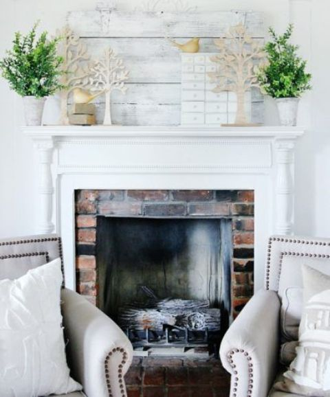a fresh and inspiring mantel with potted greenery and cardboard trees plus some birdies looks cute and rather unusual