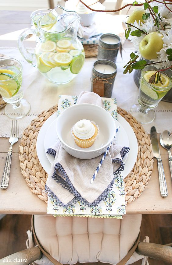 a fresh and pretty spring tablescape with woven placemats, printed napkins, white blooms and citrus drinks is very cool