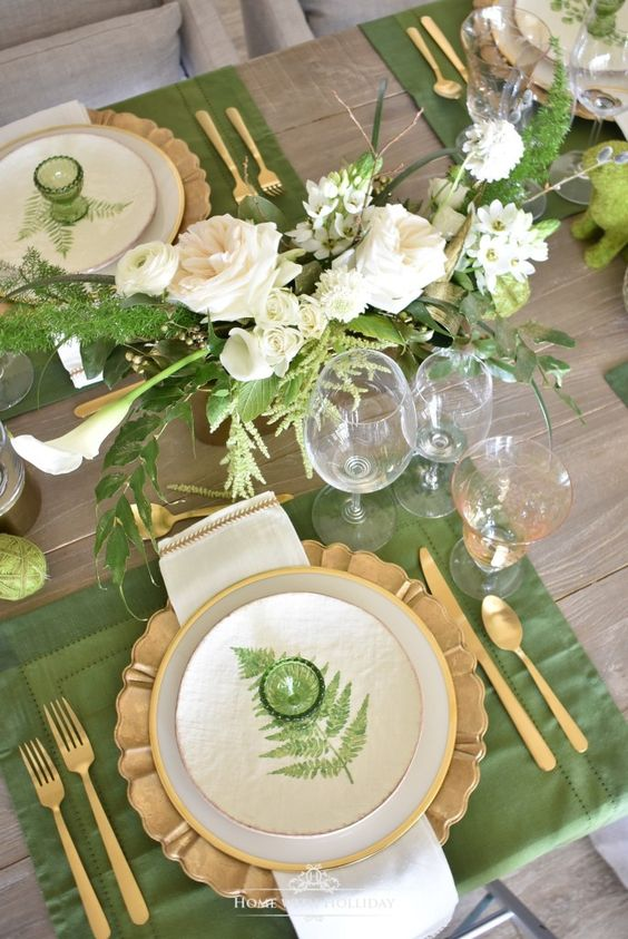 a fresh spring tablescape with white blooms and greenery, with fern-printed plates, gold cutlery and green egg holders