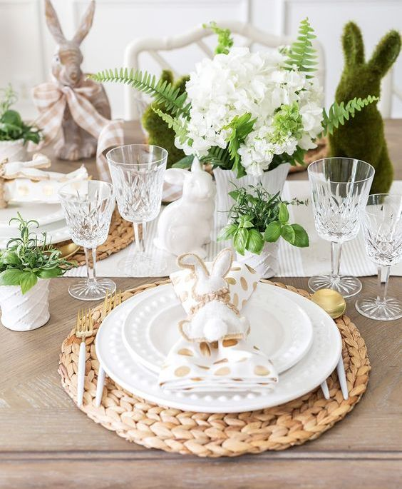 a fun Easter tablescape with a striped runner, woven chargers and printed plates, polka dot napkins, blooms and bunnies
