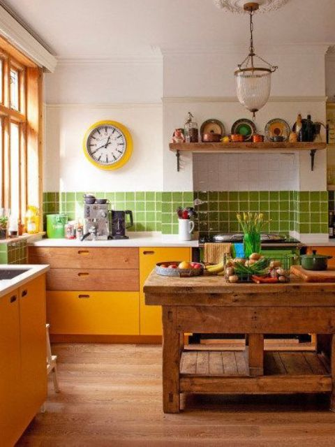 a fun and colorful kitchen with yellow cabinets, green tiles, open shelves, a rough wooden kitchen island and bold decor