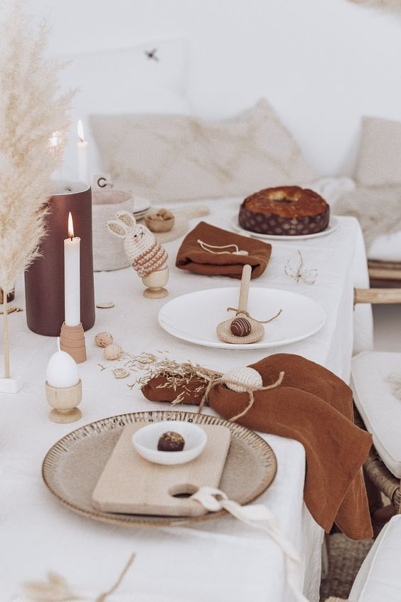 a fun modern Easter tablescape with a white tablecloth and rust-colored napkins, candles, pampas grass, wooden boards and spoons, bunny cozies for eggs