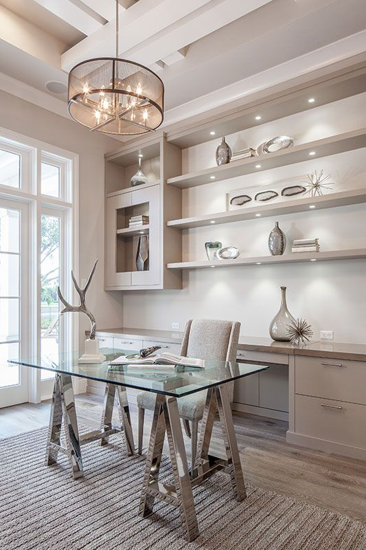 a glam and chic home office with built-in shelves and cabinets, with a second desk for storage and a pretty glass and metal trestle one
