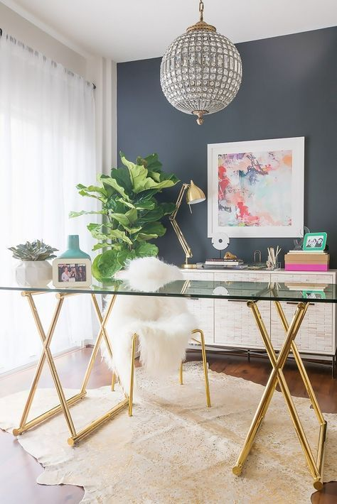 a glam home office with a glass and gold desk, a gold chair with fur, a crystal pendant lamp and bold art