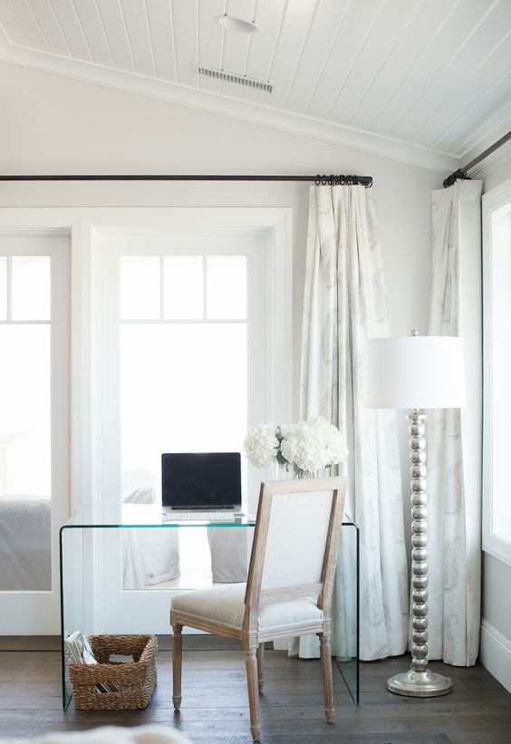 a glam rustic home office with a glass desk, a vintage farmhouse chair, a floor lamp and a basket for magazines is welcoming