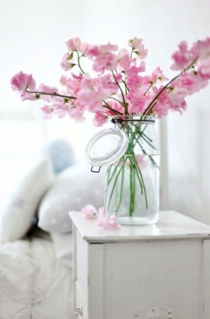 a glass jar with pink cherry blossom branches is a lovely spring centerpiece with plenty of color