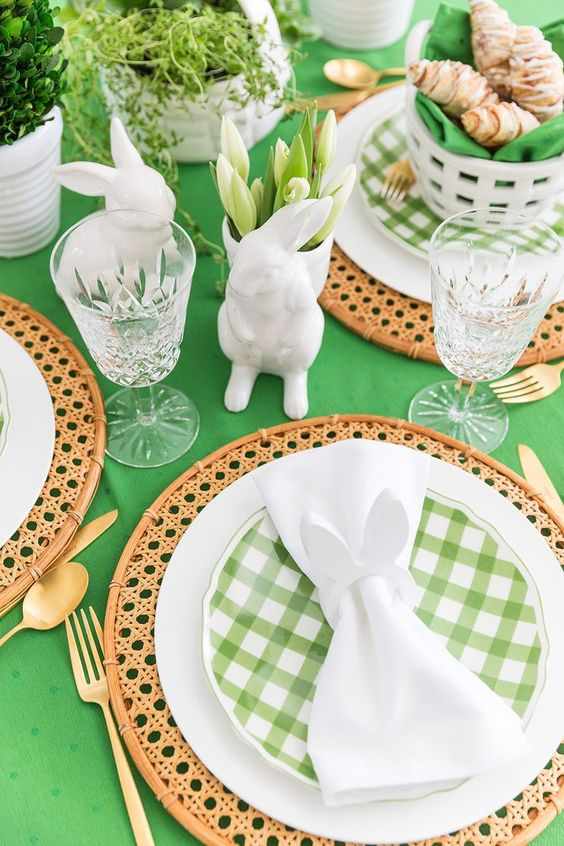 a green and white Easter tablescape with a green tablecloth, rattan placemats, green plaid plates, white tulips, bunny figurines and gold cutlery