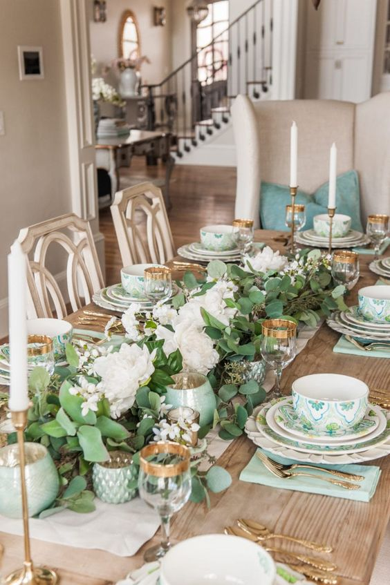 a green spring tablescape with greenery and white blooms, printed porcelain and green napkins, gold rimmed glasses and gold cutlery