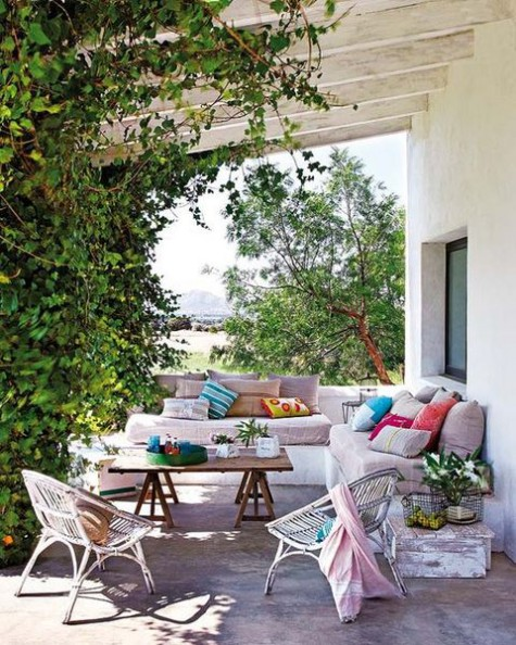 a joyful spring terrace with vines covering the pillars, a built-in corner seating and rattan chairs plus bright textiles