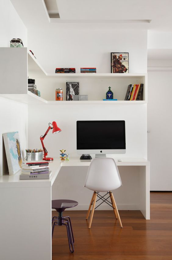 a laconic contemporary home office with an open box shelf, a corner desk, a white chair, a stool and a red lamp