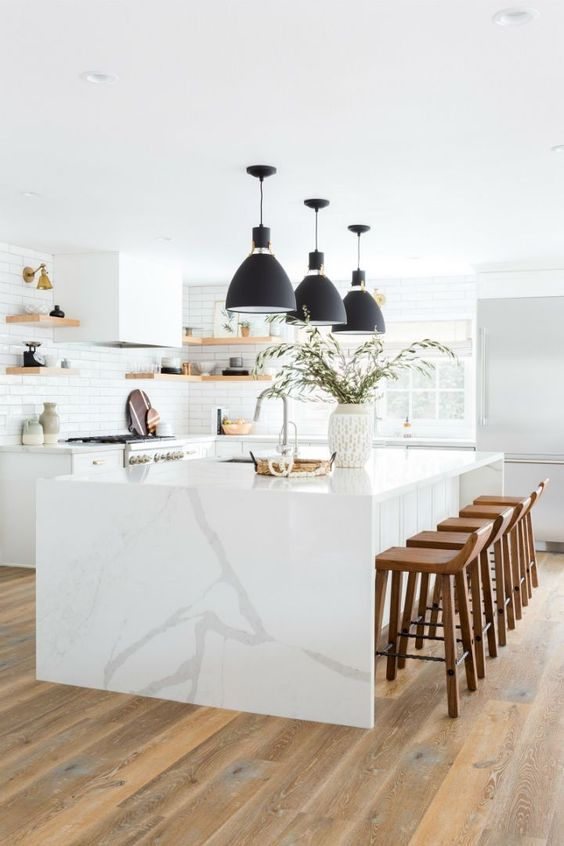 a large and airy white kitchen with elegant cabinets, a white marble island, black pendant lamps and open shelves instead of cabinetry