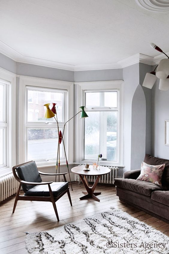 a large bay window as part of the interior, with a chair, a round table and a colorful floor lamp floods the space with light