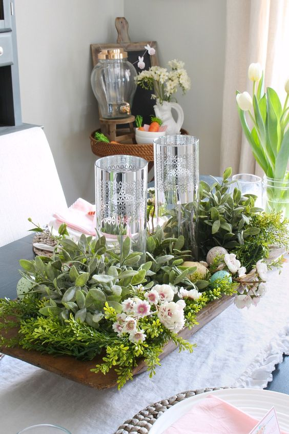 a large spring centerpiece of a wooden tray, greenery and foliage, pink blooms, faux pastel eggs and tall candleholders