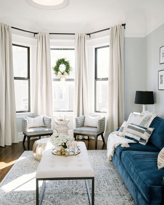 a light-filled living room with a bay window with a couple of chairs, a metallic table and ottoman, pretty creay curtains