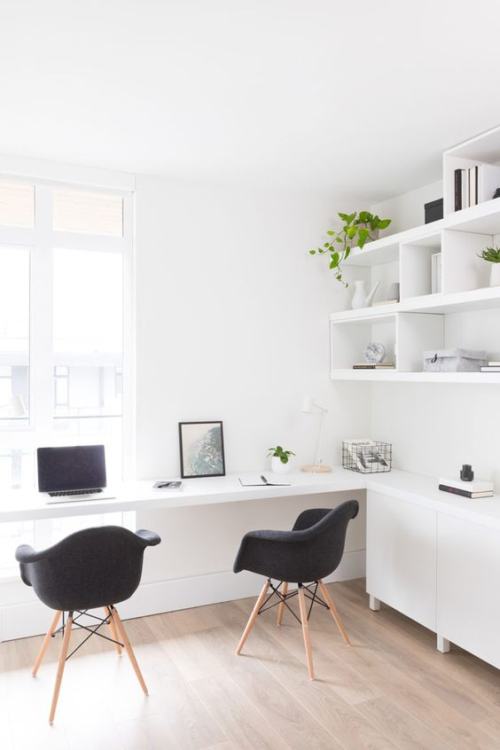 a light-filled minimalist home office with white furniture, a corner desk with a cabinet, a wall shelf unit and black chairs