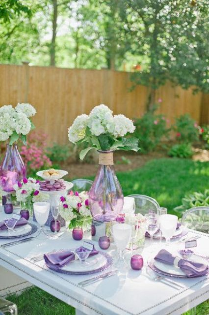a lilac or purple and white spring tablescape with purple candleholders and chargers, white blooms in lilac vases and lilac napkins