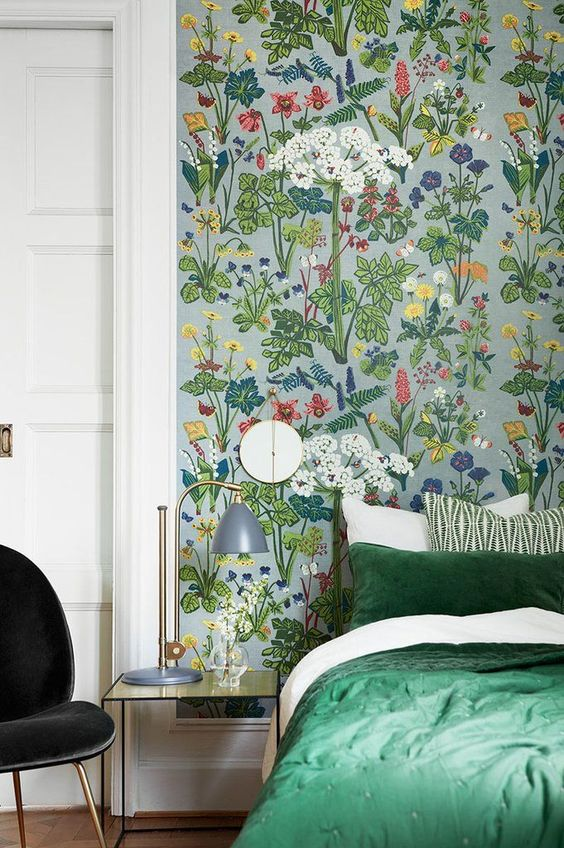 a lively and bold bedroom accented with bright floral wallpaper and with green bedding that matches the wallpaper