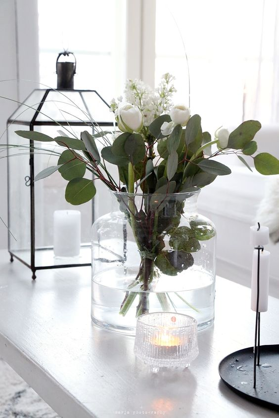 a lovely Scandinavian centerpiece with white tulips and greenery is a stylish idea for a contemporary space