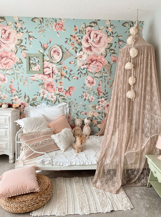 a lovely and delicate girl's bedroom with a blue and pink floral wall, a bed with a blush lace canopy, pink pillows and frames