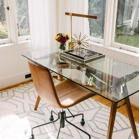 a lovely modern home office with a wood and glass trestl desk, a leather chair, a pretty lamp and a rug is cool