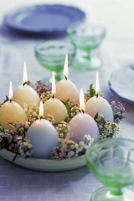 a lovely pastel spring or Easter centerpiece of a bowl with wildflowers and pastel egg-shaped candles is prety