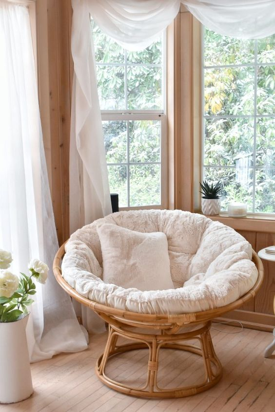 a lovely relax nook with a rattan chair with pillows, a table, potted greenery, white curtains and candles is wow
