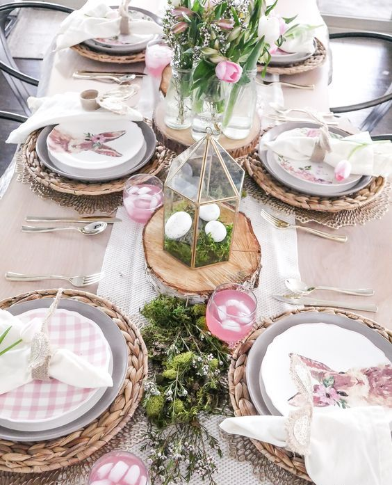 a lovely rustic Easter tablescape with woven placemats, greenery, moss, plaid plates, terrariums with moss and eggs and pink tulips