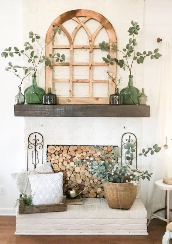 a lovely rustic spring mantel with green bottles and greenery, a vintage window frame, greenery in a basket and a wood slice screen on the fireplace
