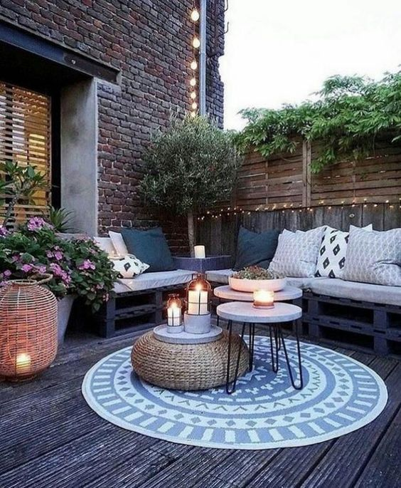 a lovely spring Scandinavian terrace with a black pallet corner seating, printed pillows and a rug, a woven ottoman and round tables