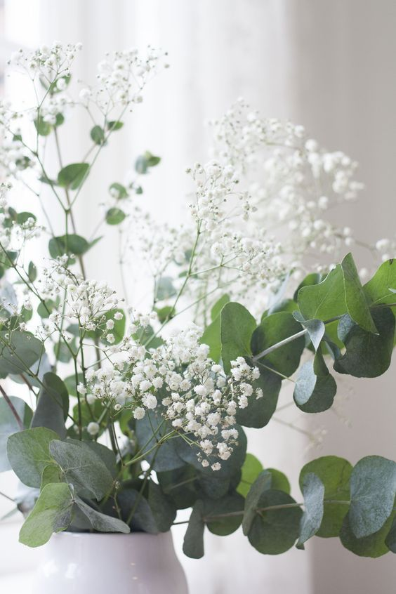 a lovely spring arrangement with eucalyptus, gypsophilia is a fresh and non-typical idea for decorating a table