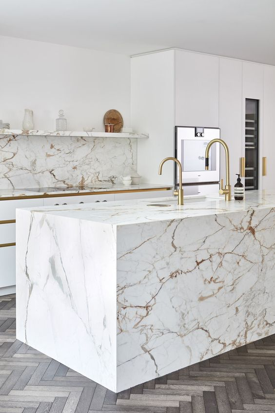 a luxurious white kitchen with sleek cabinetry, a white marble backsplash and island, gold touches looks jaw-dropping