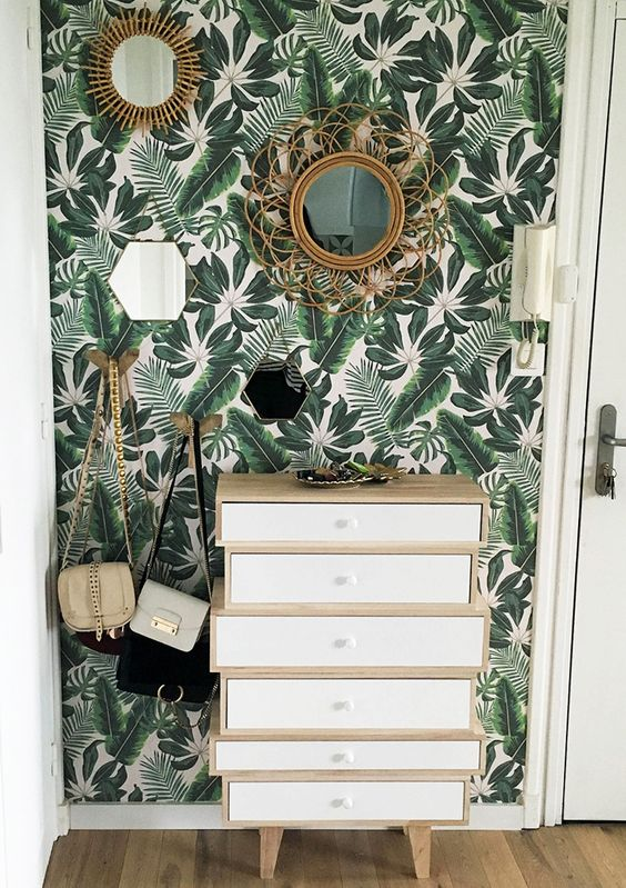 a mid century modern entryway with a botanical wall, a pretty little storage unit, a couple of mirrors and some hooks for bags
